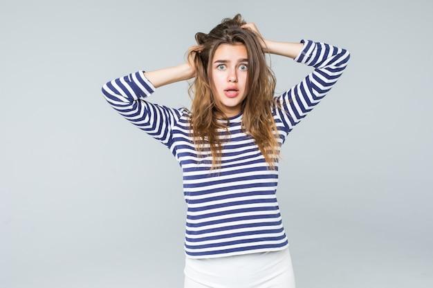 Een gefrustreerde en boze vrouw schreeuwt hardop en trekt haar haar dat op witte achtergrond wordt geïsoleerd