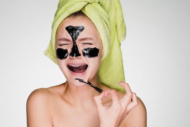 Een gefrustreerde vrouw haalt een schoonmaakmasker van haar gezicht