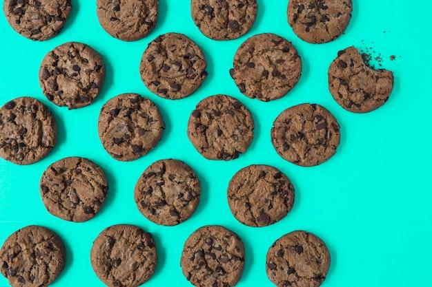 Één gegeten koekje onder de verse gebakken koekjes op turkooise achtergrond