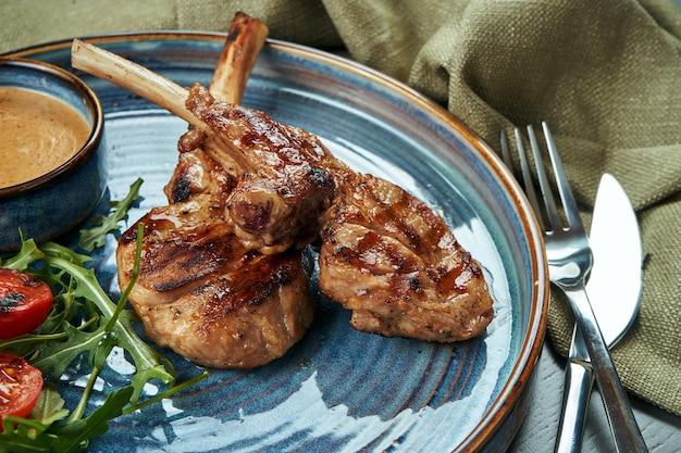Een gegrilde rek van jonge kalf of lam (rundvlees) met pindasaus en cherrytomaatjes in een blauw bord op een houten oppervlak. selectieve aandacht, close-up