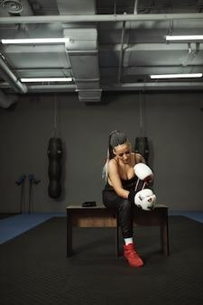 Een gehandicapt meisje houdt zich bezig met de sportschool. een vrouw met één been traint met een trainer in boksen, ze leert vechten