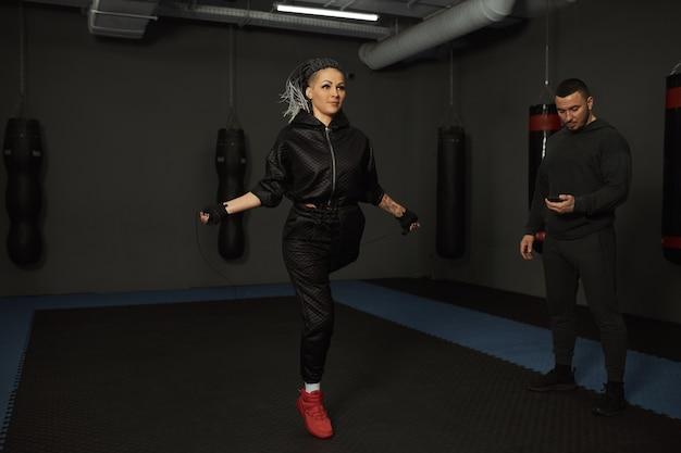 Een gehandicapt meisje is bezig met de sportschool een vrouw met één been traint met een trainer, ze werkt hard en geeft niet op voor problemen