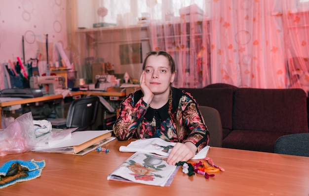 Een gehandicapt meisje met scheve ogen zit aan een tafel en glimlacht. mensen met een handicap.