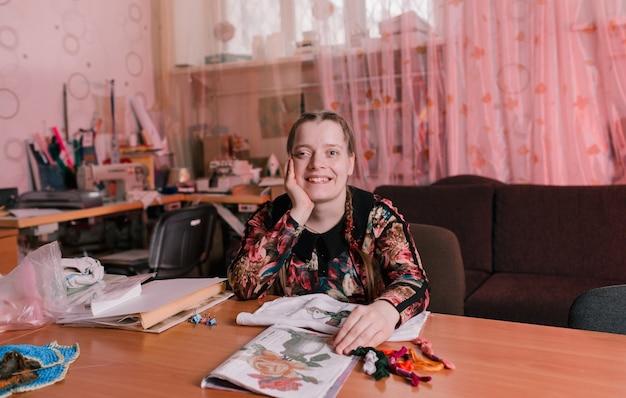 Een gehandicapt meisje met scheve ogen zit aan een tafel en lacht. mensen met een handicap.
