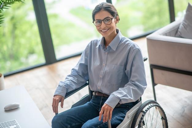 Een gehandicapte jonge vrouw die er tevreden uitziet en vriendelijk lacht