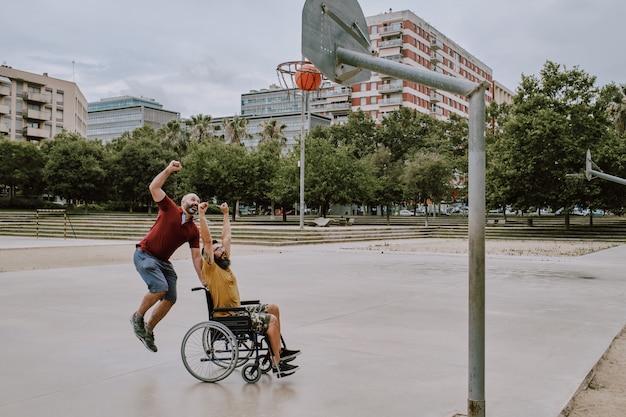 Een gehandicapte man in rolstoel speelt mand met een vriend