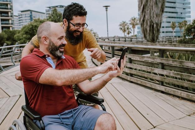 Een gehandicapte man op rolstoel met zijn assistent op zoek naar een mobiele telefoon