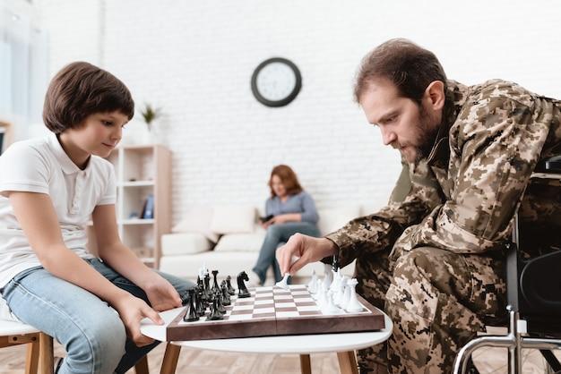 Een gehandicapte man speelt met zijn zoon in het schaakspel.
