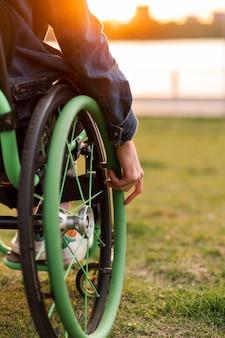Een gehandicapte man zit in een rolstoel hij houdt zijn handen aan het stuur foto van hoge kwaliteit