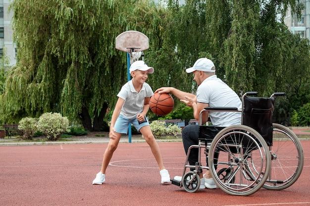 Een gehandicapte vader speelt met zijn zoon op straat. rolstoelconcept, gehandicapte, vervullend leven, vader en zoon, activiteit, opgewektheid.