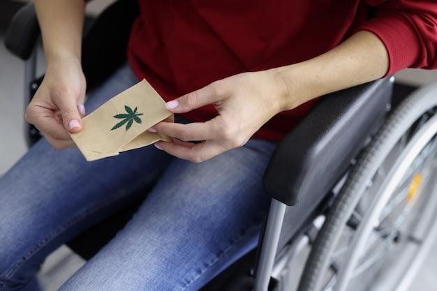 Een gehandicapte vrouw houdt een pakketje met marihuana vast