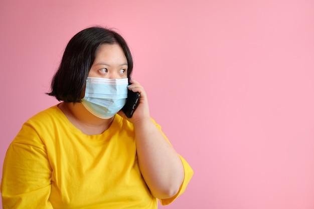 Een gehandicapte vrouw met het syndroom van down leert met een mobiele telefoon gebaren aan de telefoon ze is een gehandicapte student met het syndroom van down die een medisch masker draagt