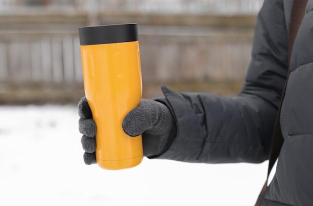 Een gehandschoende hand houdt een gele thermoskan vast met een warme drank