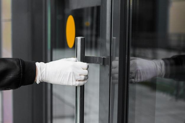 Een gehandschoende hand opent de deur op straat. man in handschoenen heeft een deurknop