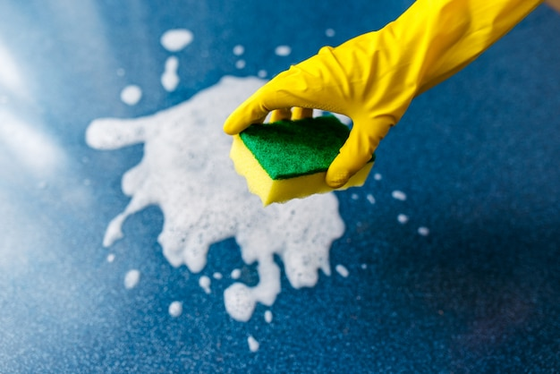 Een gehandschoende hand veegt schuim en vuil af met een washandje. het schoonmaken.