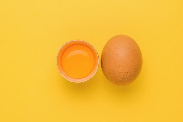 Een geheel en gebroken bruin kippenei op een gele achtergrond. een natuurproduct.