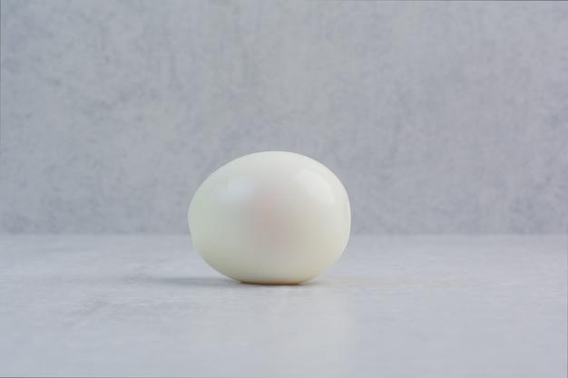 Een geheel gekookt ei op een grijze achtergrond.