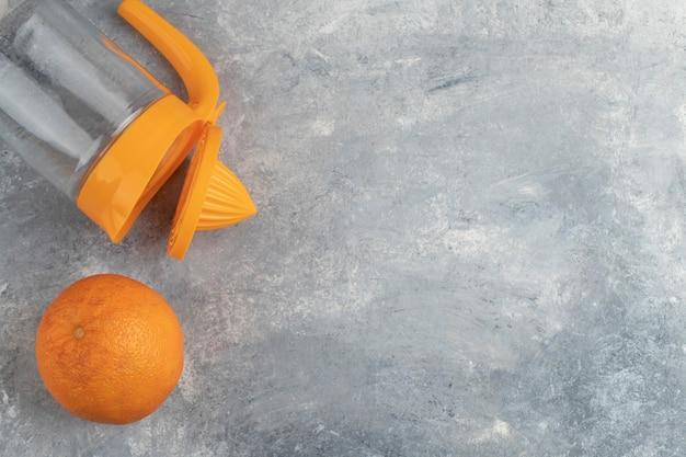 Één geheel gezond oranje fruit met een lege glaswaterkruik op marmeren achtergrond.