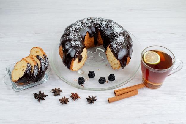 Een geheel van de vooraanzichtchocoladecake en gesneden met kaneel en thee op het witte cakekoekje als achtergrond