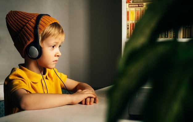 Een geïnteresseerde kleine schooljongen met een gele hoed en koptelefoon zit aan zijn thuistafel en kijkt toe
