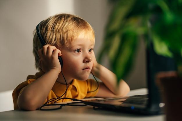 Een geïnteresseerde kleine schooljongen met een koptelefoon zit aan zijn thuisbureau en kijkt naar een videotuto