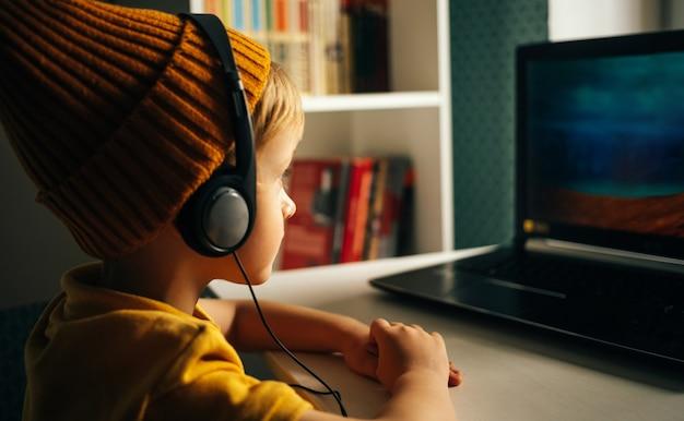 Een geïnteresseerde kleine schooljongen met koptelefoon zit aan zijn thuisbureau aandachtig te kijken
