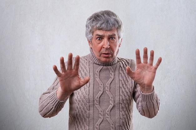 Een geïrriteerde volwassen man met een verbaasde en boze uitdrukking die iets weigert terwijl hij geen teken vertoont met zijn handpalmen