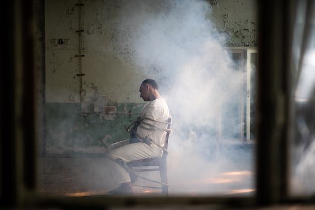 Een gekke man in een keurslijf zit vastgebonden op een stoel in een verlaten oude kliniek.
