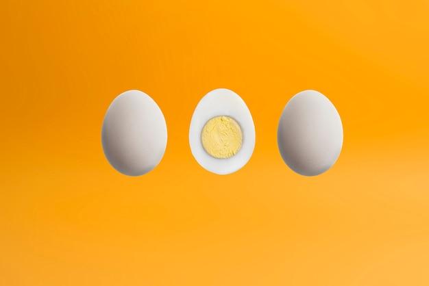 Een gekookt gekookt ei dat op pastelkleurenachtergrond wordt geïsoleerd