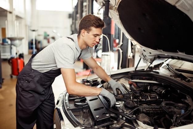 Een gekwalificeerde automonteur is op zoek naar bugs bij een autoreparatieservice.