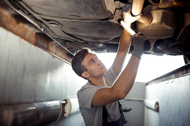 Een gekwalificeerde automonteur voert een onderzoek uit van een opgetilde auto.