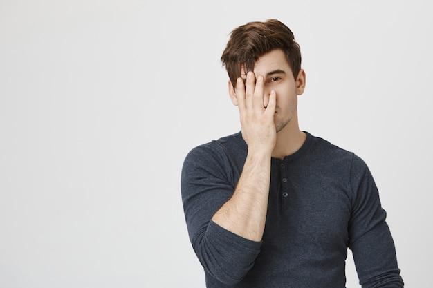 Een gekwelde en geïrriteerde man bedekt zijn gezicht met zijn handpalm