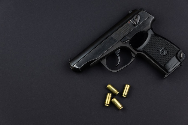 Een geladen pistool en zijn patronen liggen naast elkaar op een zwart oppervlak