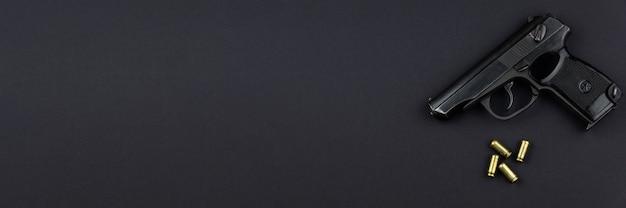 Een geladen pistool en zijn patronen liggen naast elkaar op een zwarte achtergrond