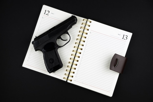 Een geladen traumatisch pistool ligt op een geopend notitieboekje op een zwart oppervlak
