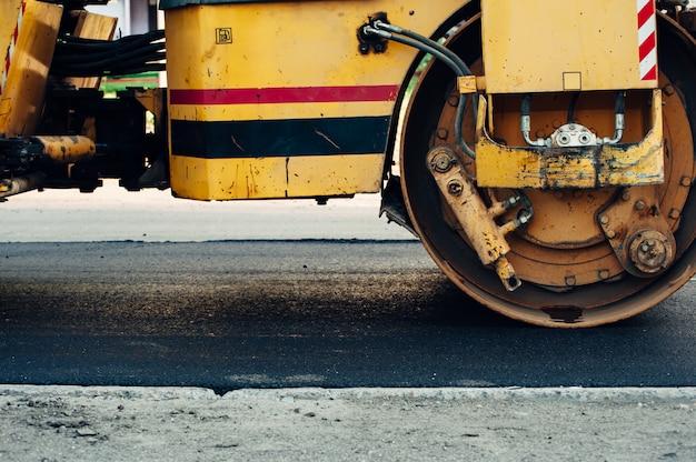 Een gele asfaltverdichter lijnt de weg uit. nieuw asfalt leggen.