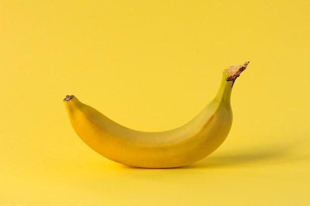 Een gele banaan staat.