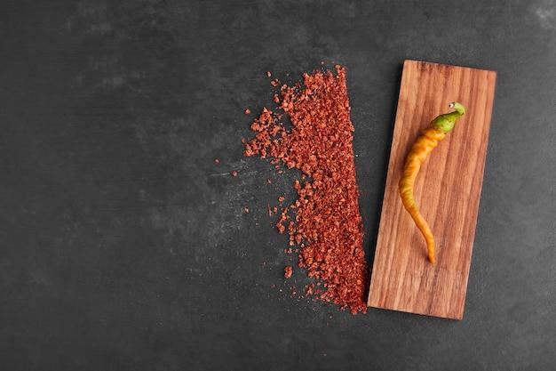 Een gele chili op een houten schaal met paprika opzij.