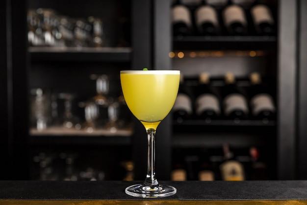 Een gele cocktail in een nick en nora glas gegarneerd met koriander aan de bar
