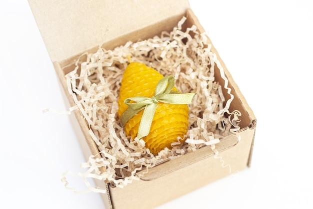 Een gele decoratieve natuurlijke bijenwaskaars met een honingaroma voor interieur in de vorm van een paasei met een groen lint in een kartonnen geschenkdoos