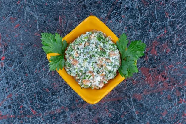 Een gele diepe plaat met heerlijke salade en kruiden.
