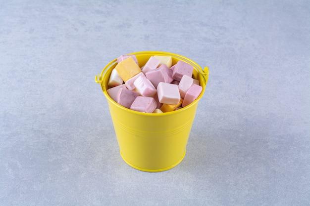 Een gele emmer met roze en gele zoete zoetwaren pastila