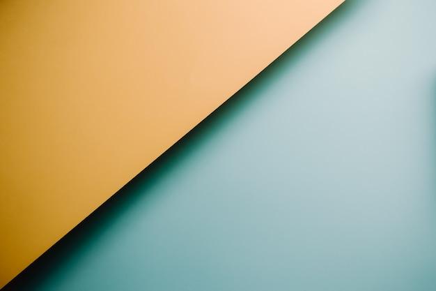 Een gele en blauwe pastel plat lag achtergrond met scherpe lagen en schaduwen met kopie ruimte