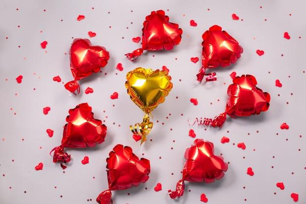 Een gele en vele kleine rode luchtballonnen van hartvormige folie