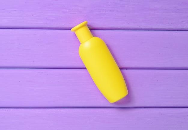 Een gele fles shampoo op een paarse houten tafel.