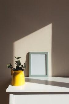 Een gele keramische kruik of vaas met eucalyptustakken, lege witte fotolijsten op de witte tafel in het interieur met beige muren bij raam.