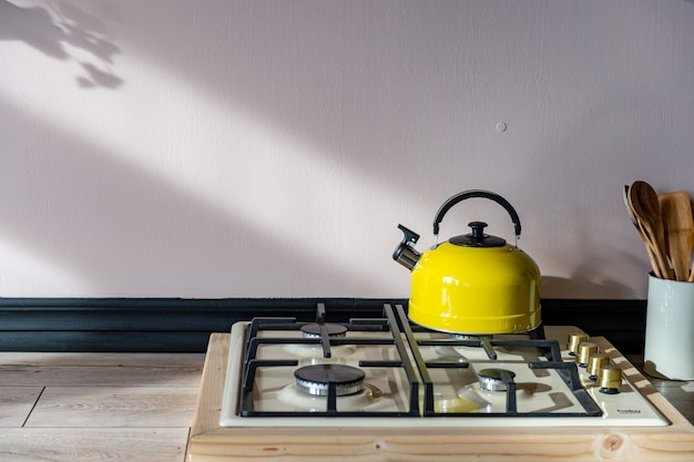 Een gele ketel met een zwart handvat staat op een gasfornuis.
