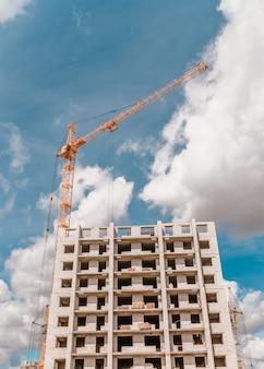 Een gele kraan bouwt een gebouw met meerdere verdiepingen tegen de blauwe lucht.