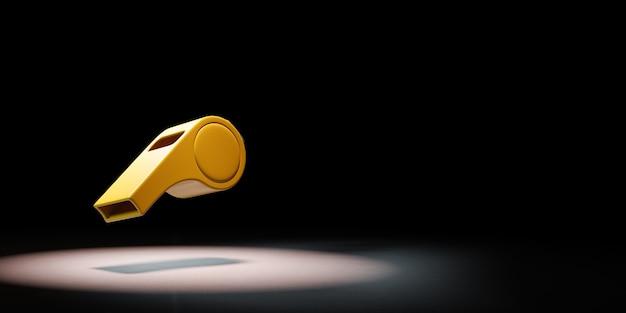Een gele plastic fluitje in de schijnwerpers op zwarte achtergrond
