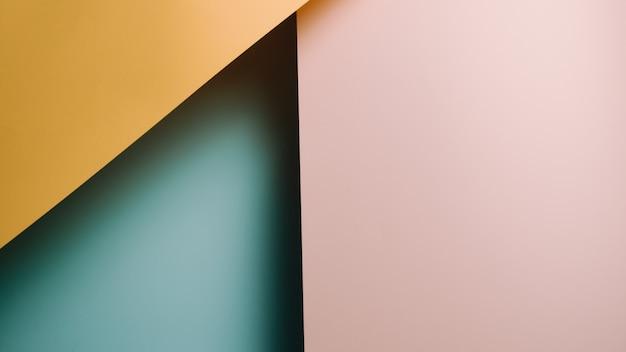 Een gele, roze en blauwe pastel plat lag achtergrond met scherpe lagen en schaduwen met kopie ruimte